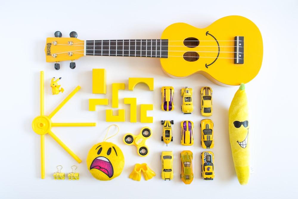 yellow ukulele, cars, emoji plush toy on white surface