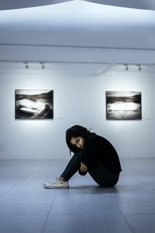 woman sitting on white tiles