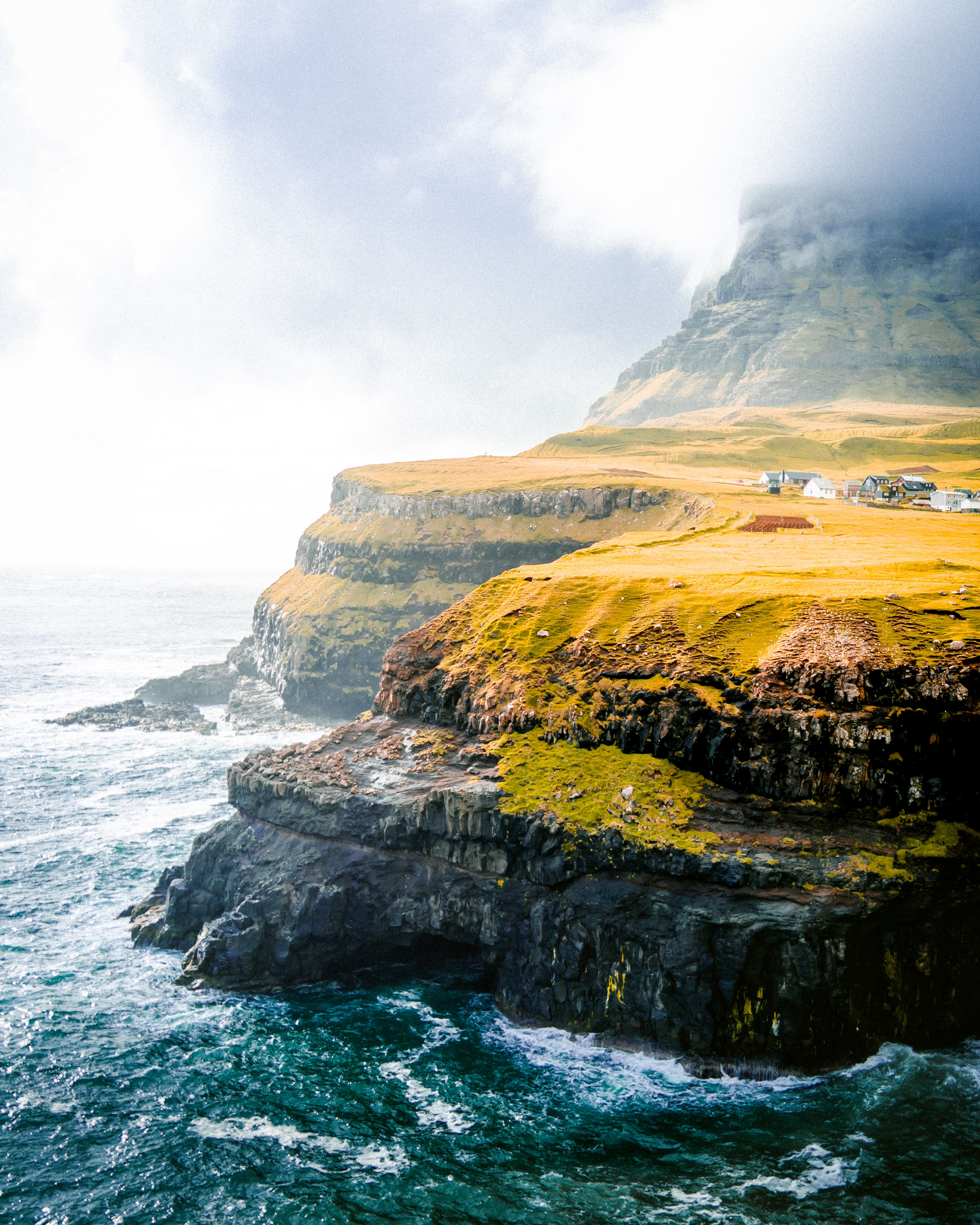 nature photography of sea cliff under cloudy sky during daytime