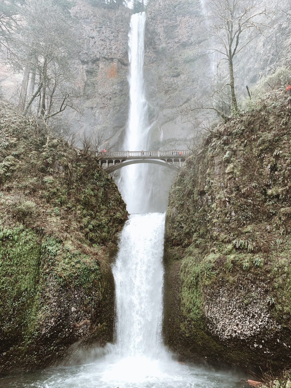 time lapse photography of waterfalls under bridge