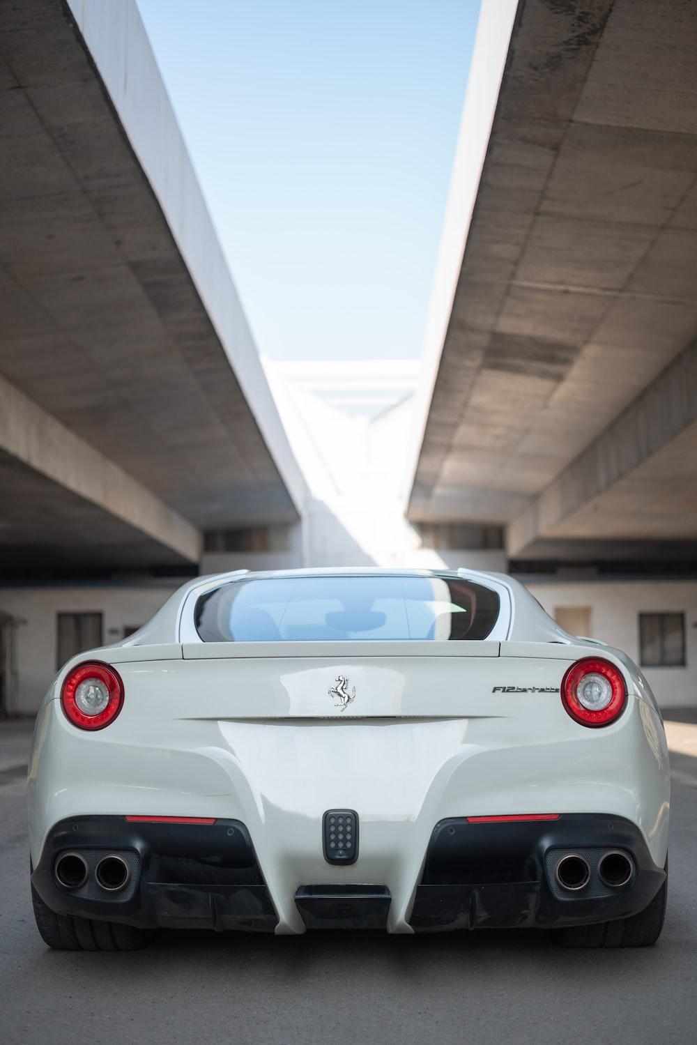 white Ferrari vehicle parked under bridge