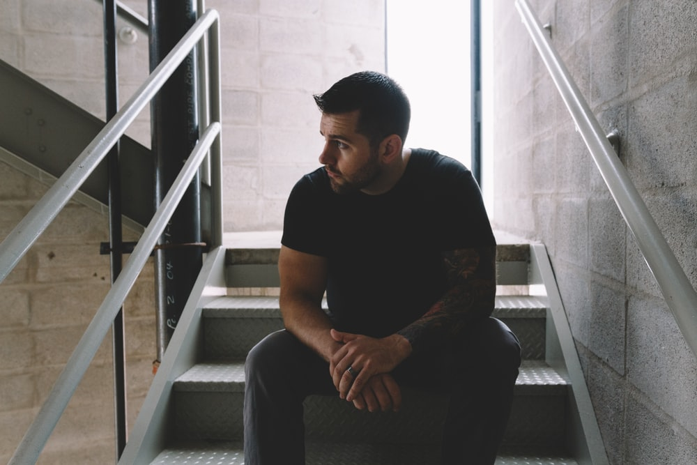 man in black crew-neck shirt sitting on staircase