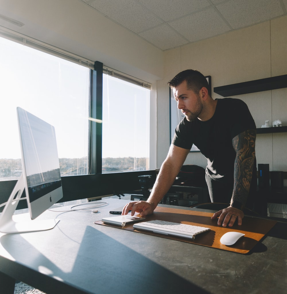man in black shirt standing and using computer inside office during daytime