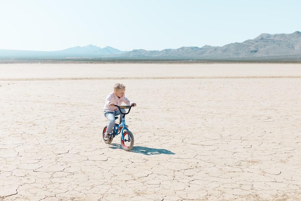 toddler riding bike on dry soil