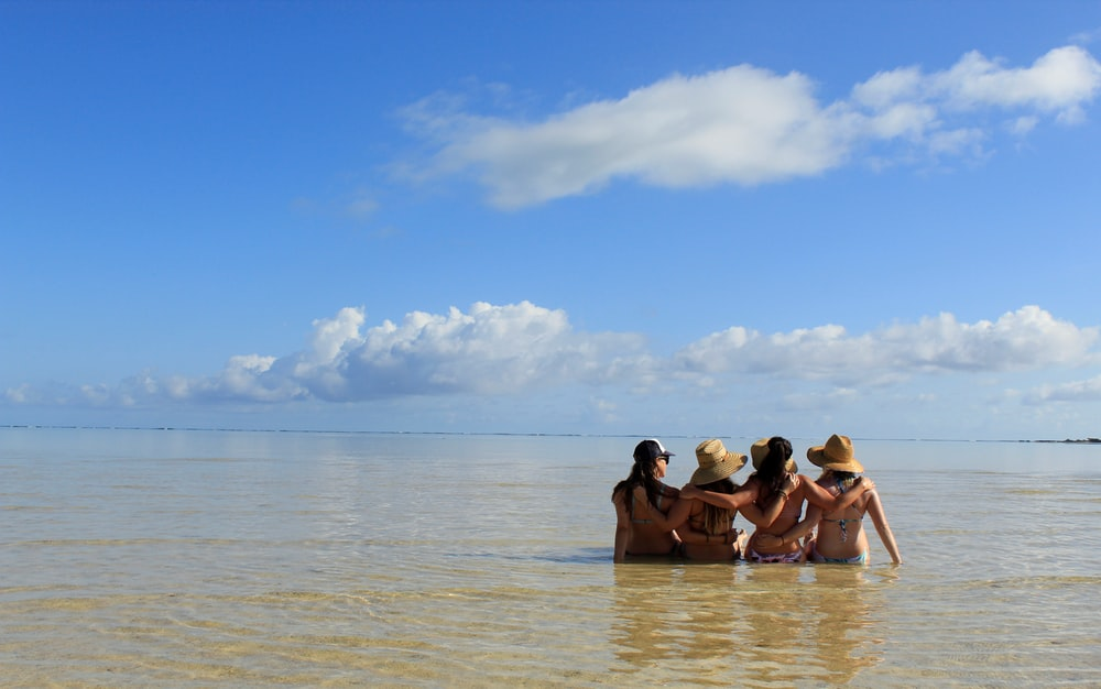 four women sitting on body of water during daytime