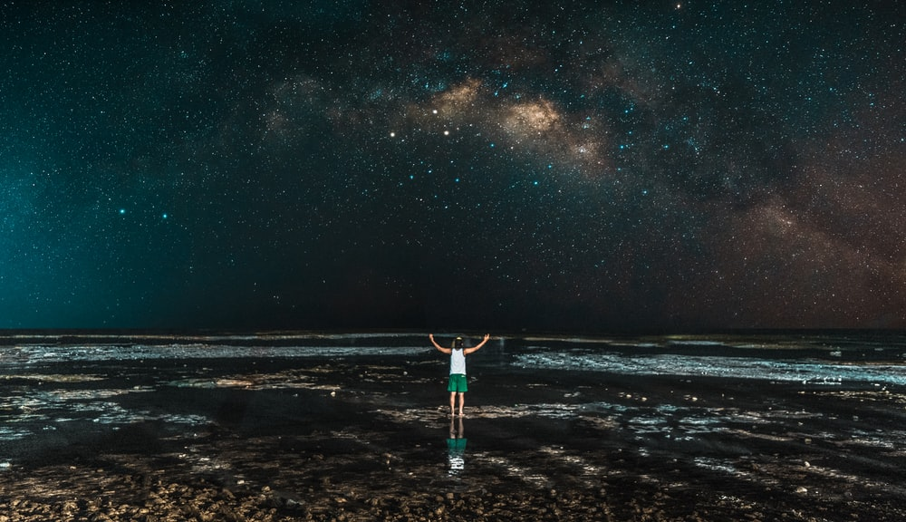 person standing in front of sea during nighttime