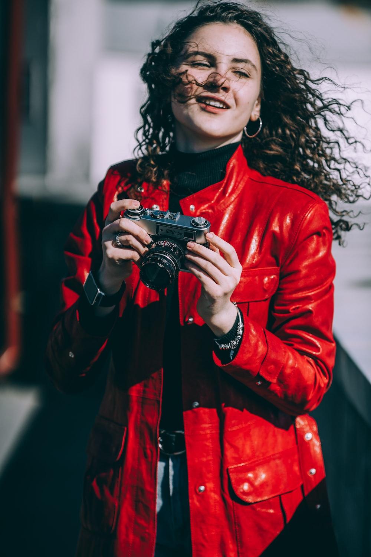 woman holding gray camera