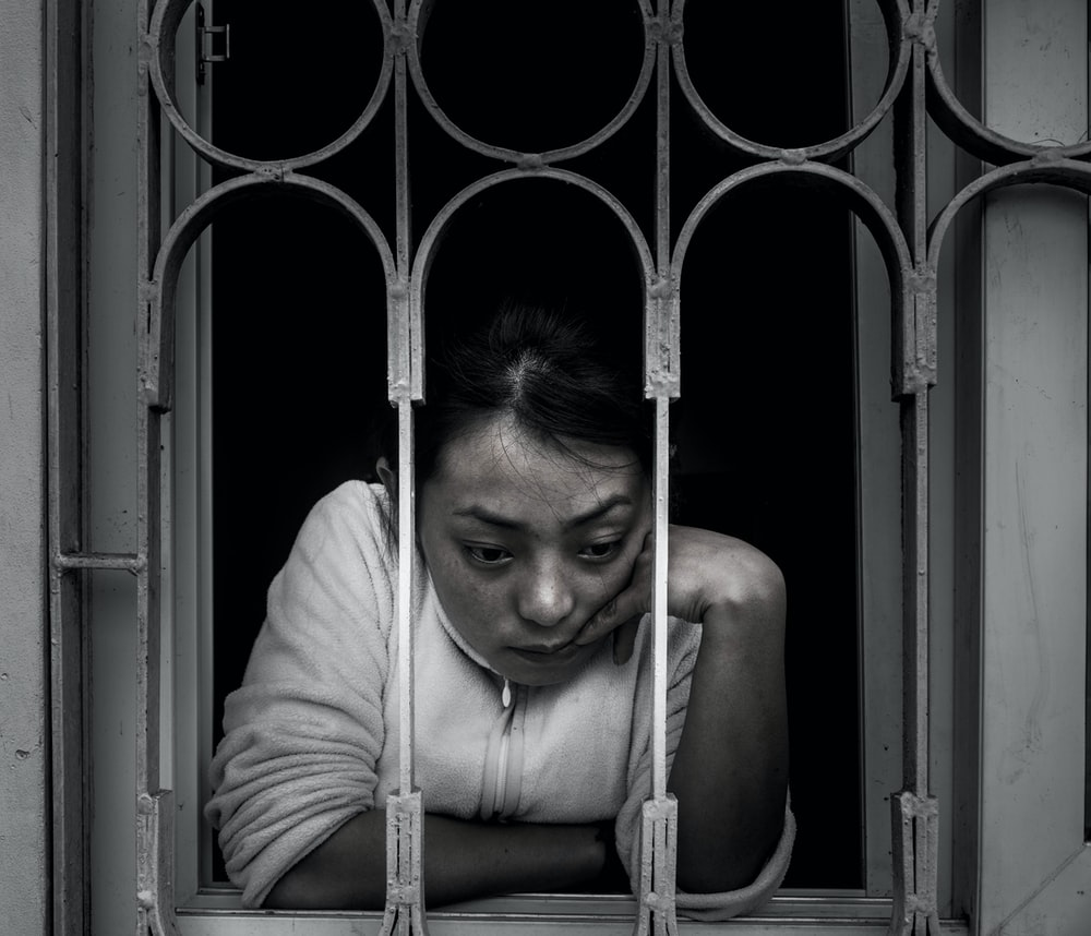 grayscale photography of woman looking out a window