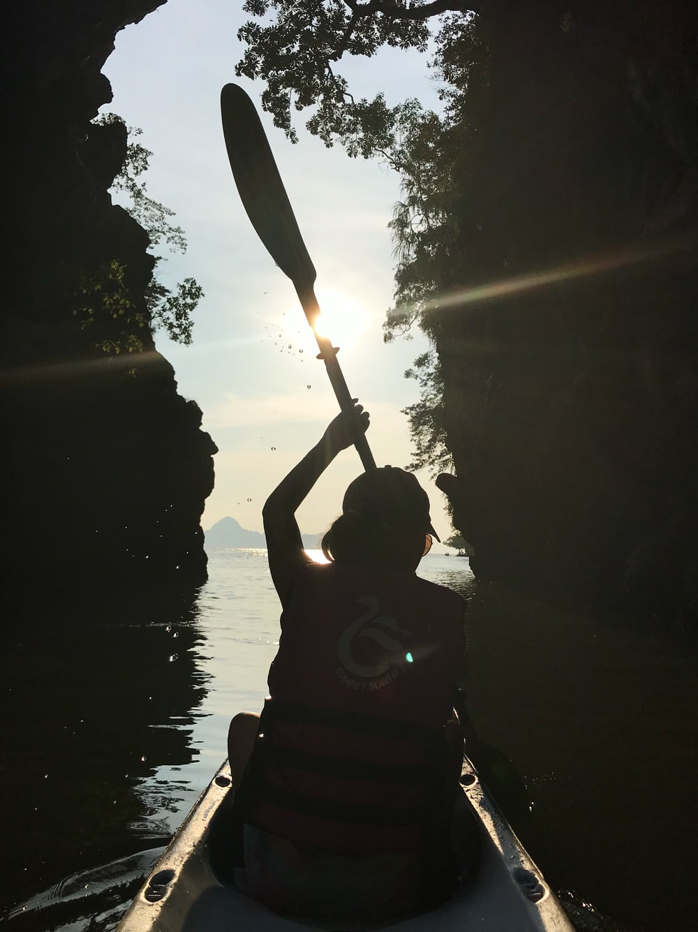 silhouette photography of man holding boat paddle