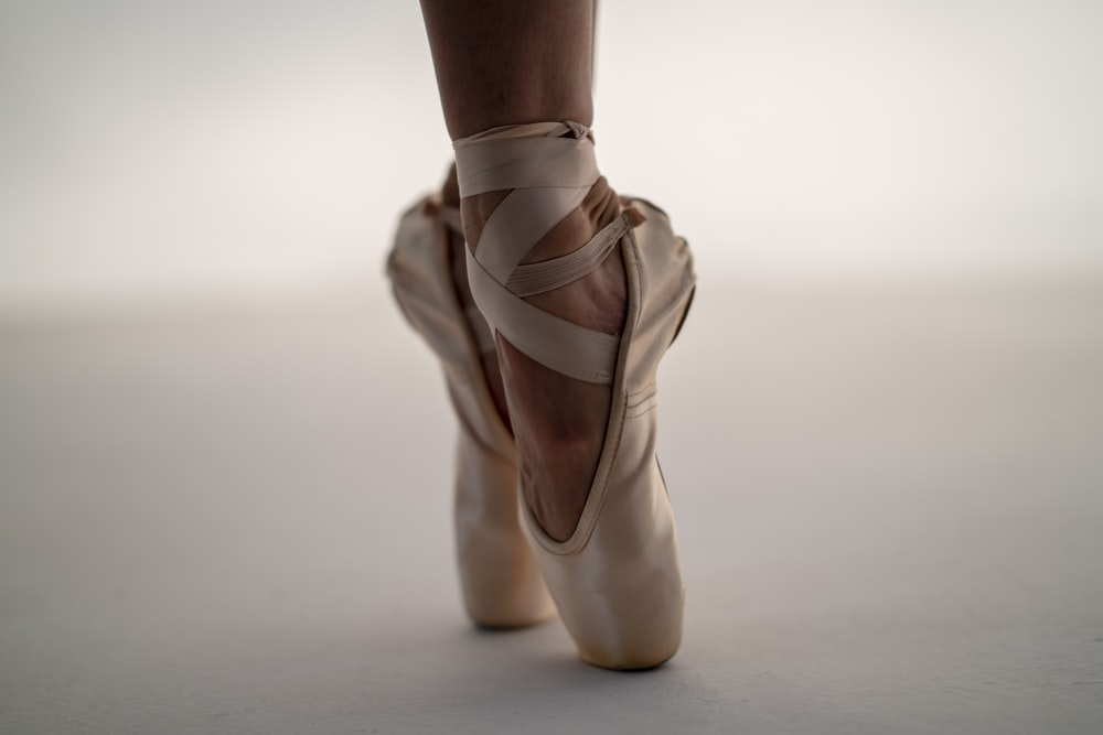 person in white ballet shoes