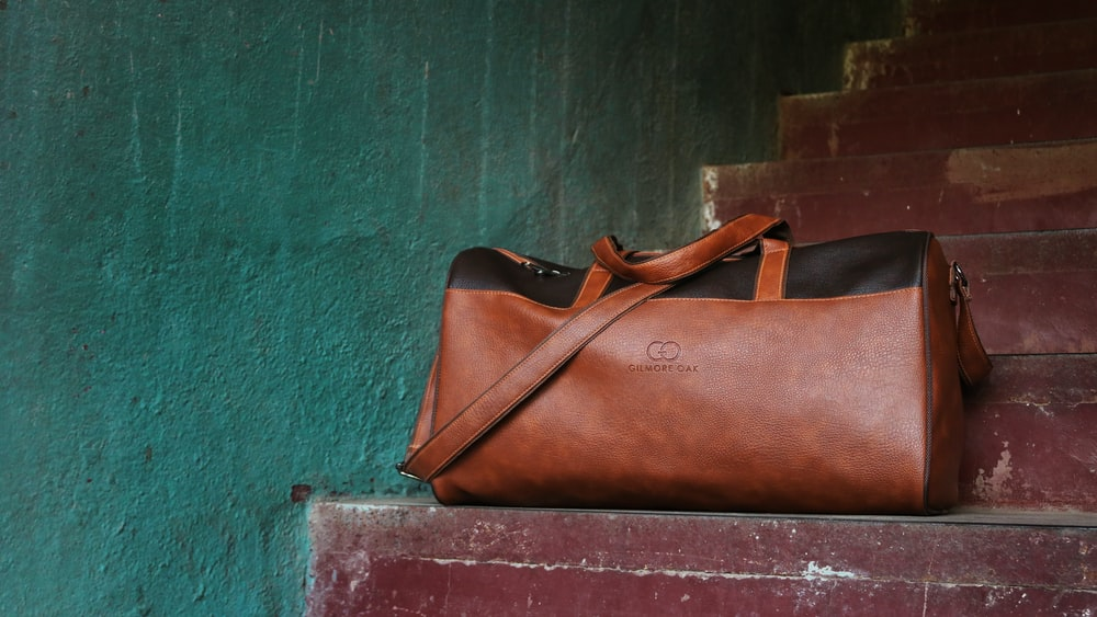 brown Gucci leather duffel bag on brown stair