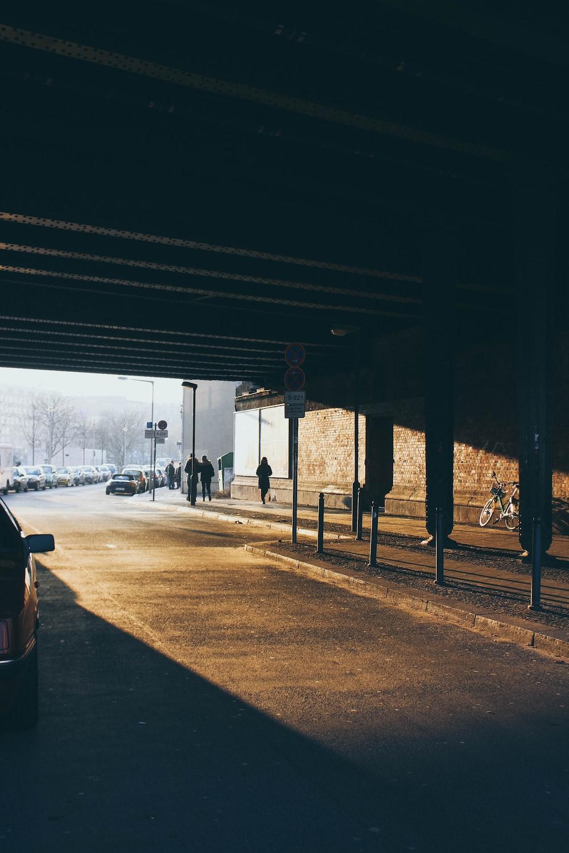 people walking underneath bridge