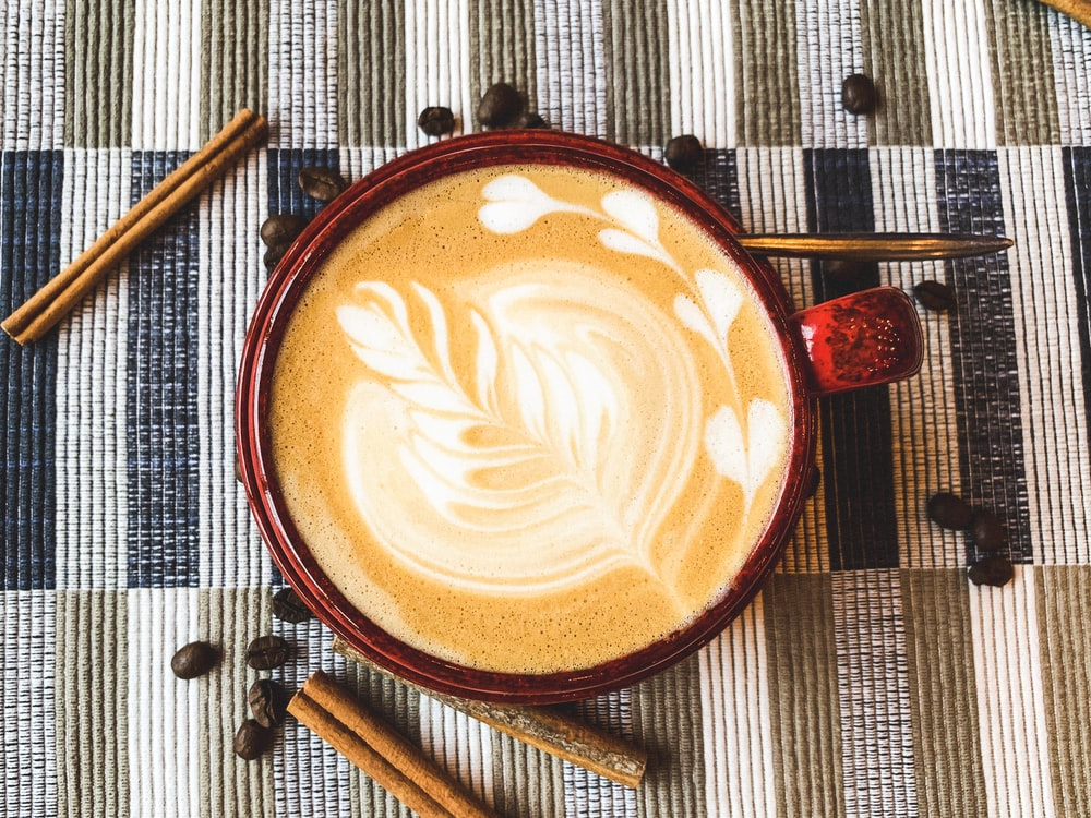 flat lay photography of coffee latte with art