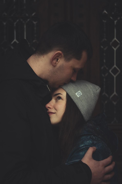 man kissing woman's forehead