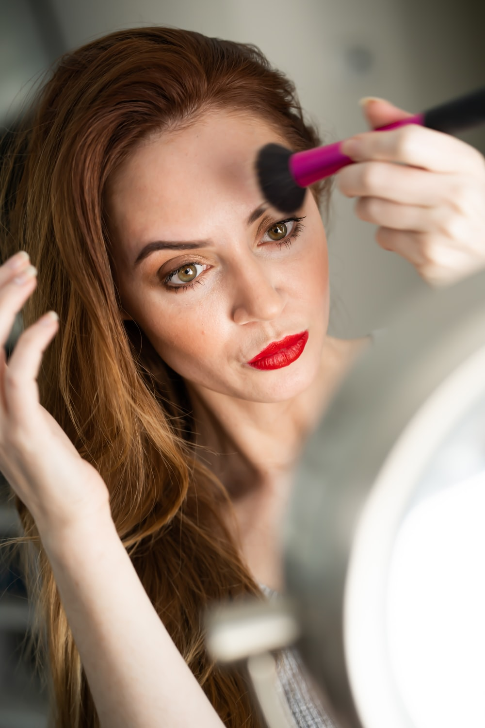 woman facing mirror holding makeup brush