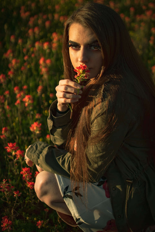 woman wearing brown jacket holding flower