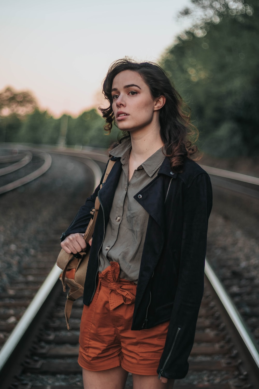 woman standing in the middle of railway