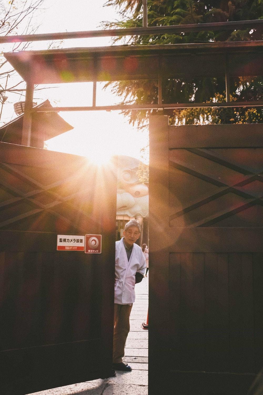 man standing beside metal gate during golden hour