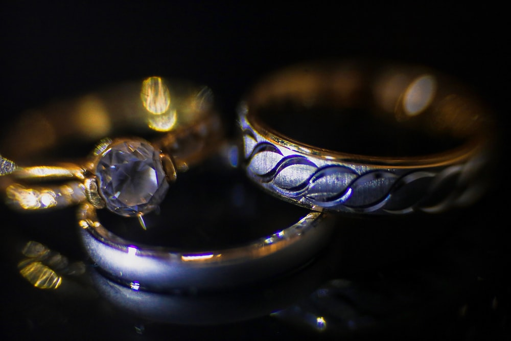 silver and gold rings on black surface