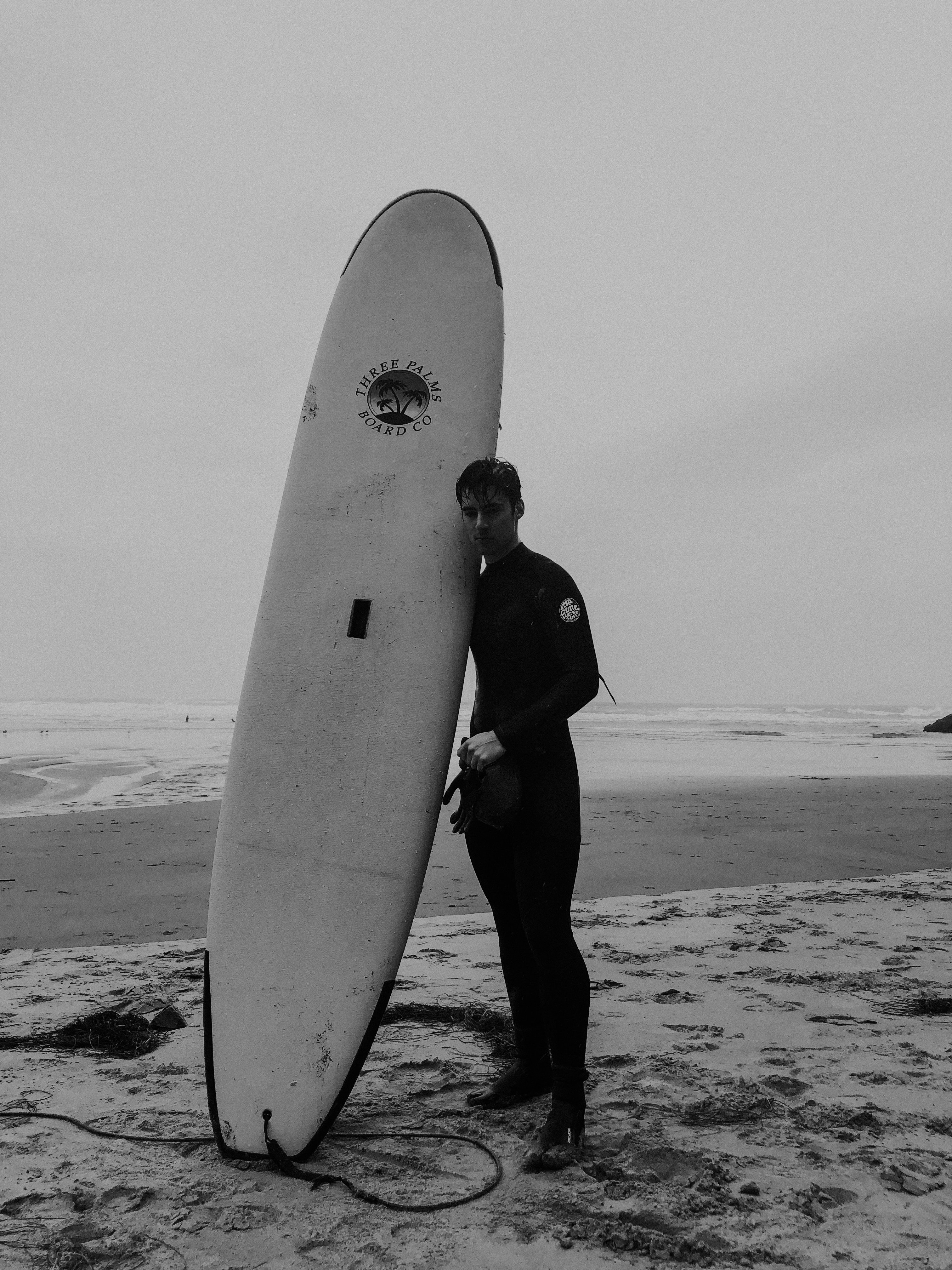 man standing on shore holding surfboard