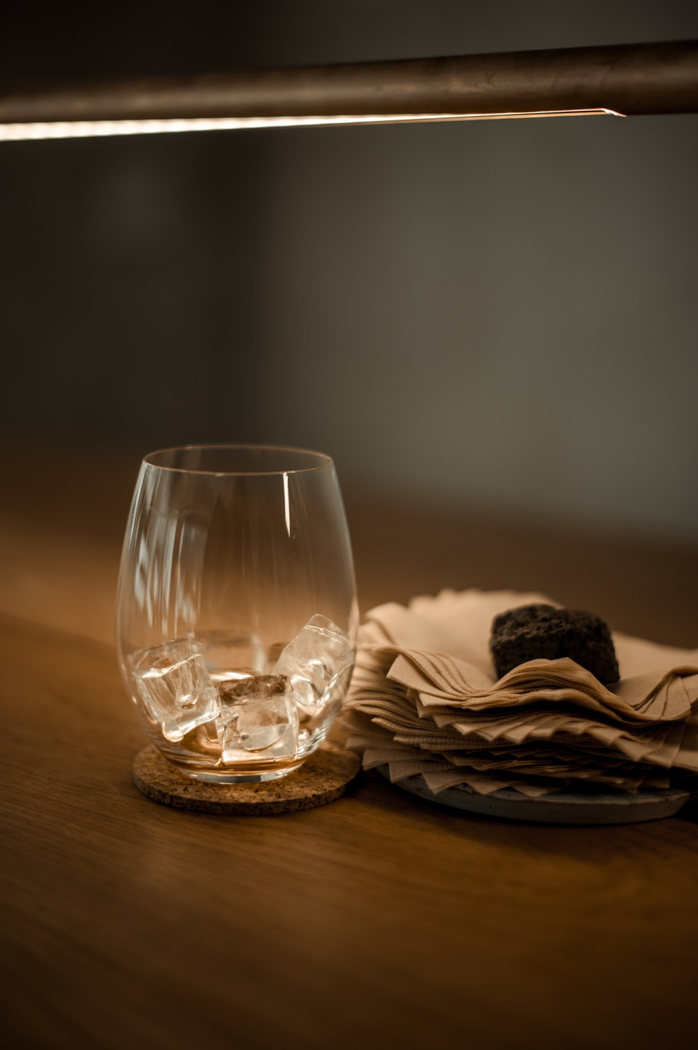 clear drinking glass beside paper