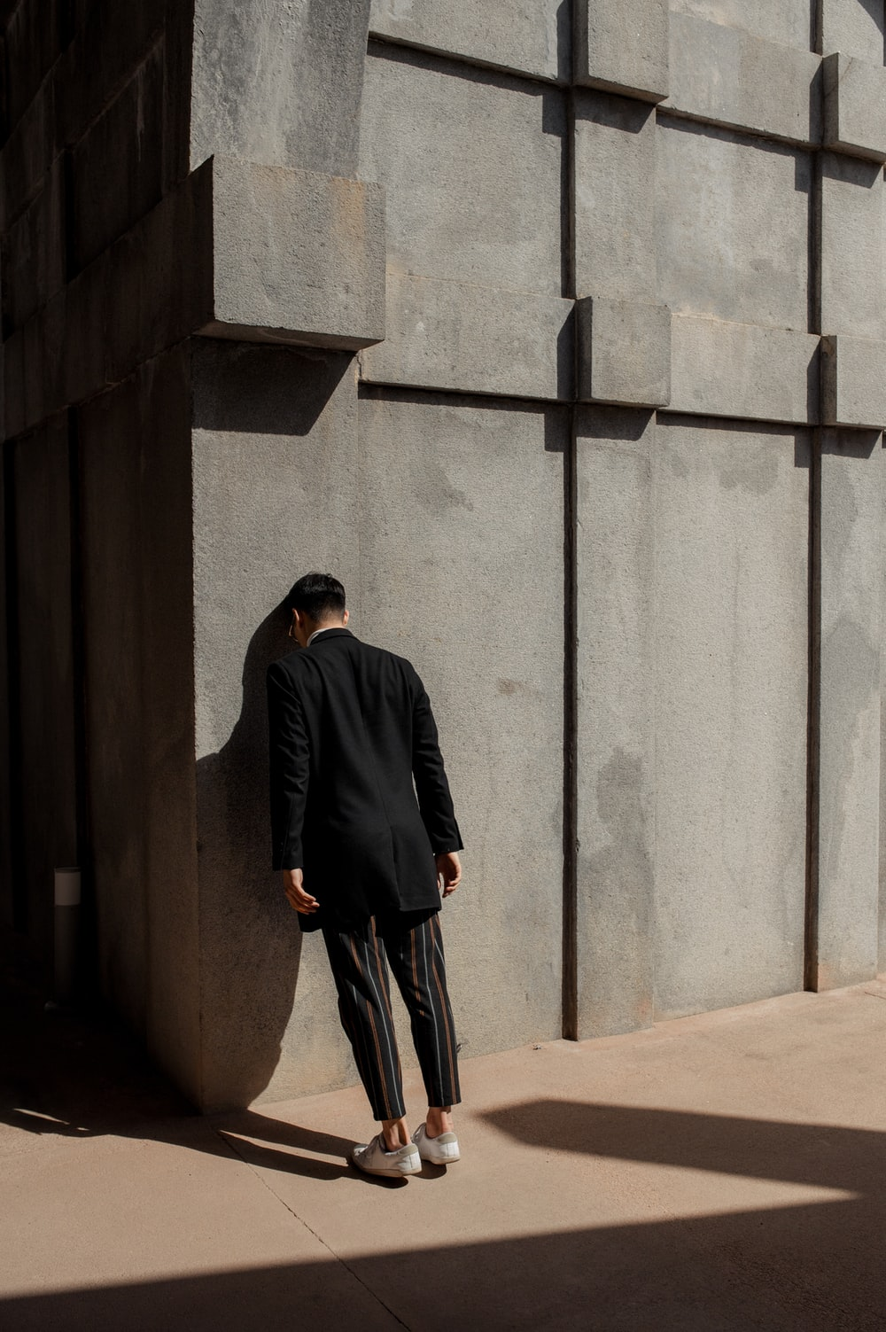 man in black suit banging his head on wall