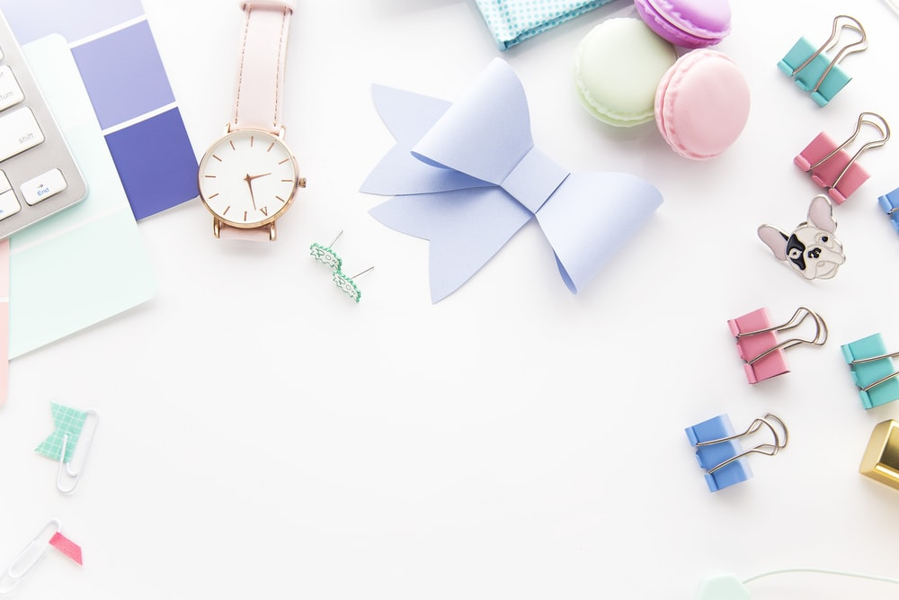 round white and gold-colored analog watch beside paper ribbon