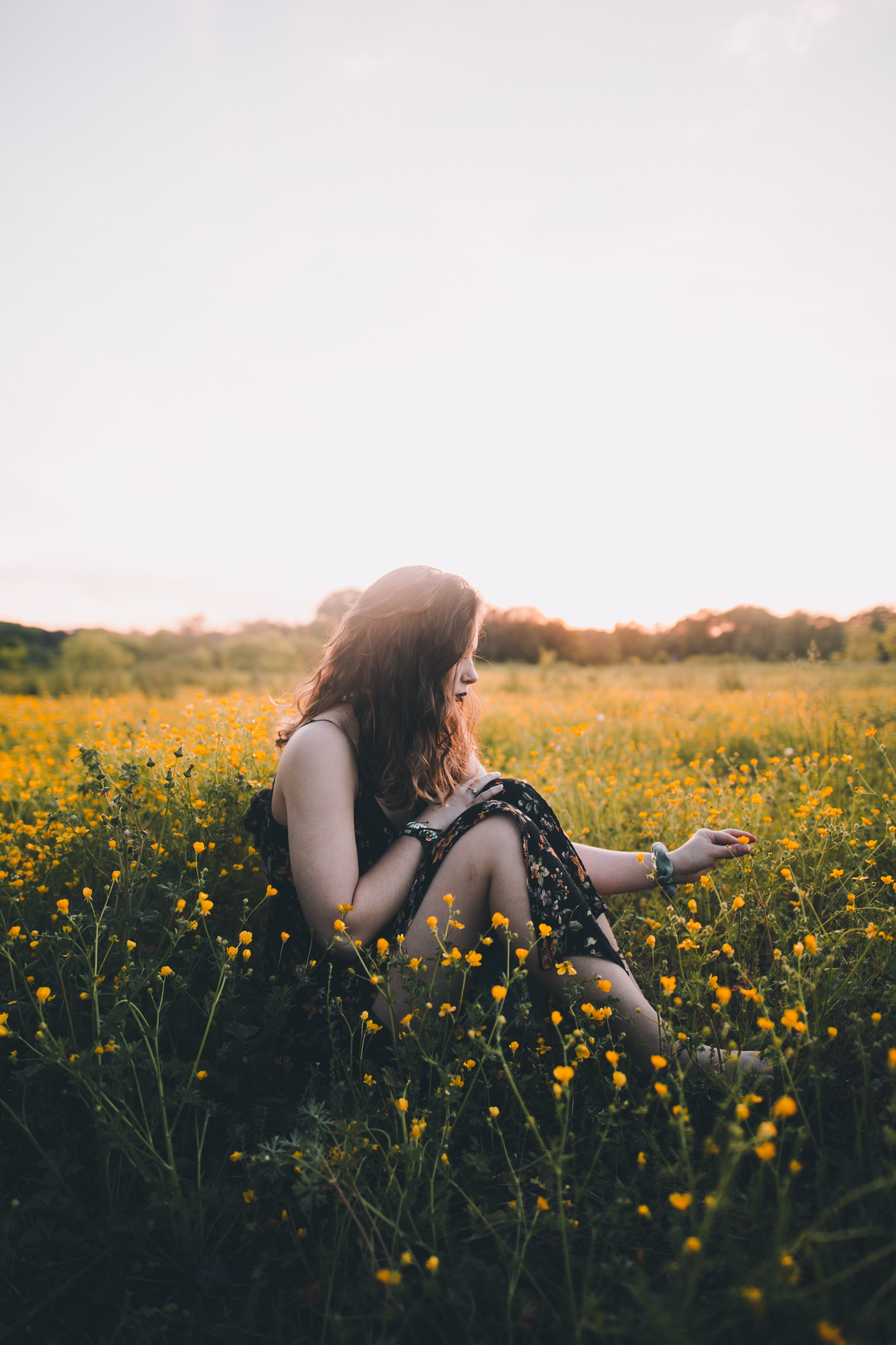woman sitting on bed of flower