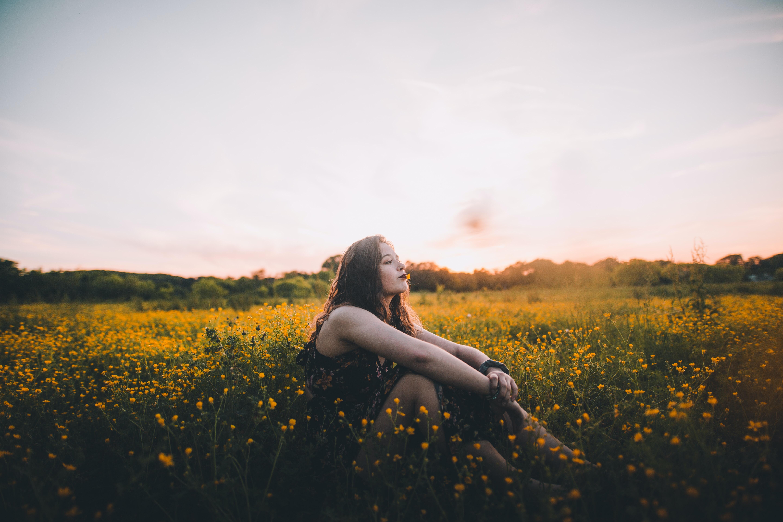 woman sitting on yellow flower field