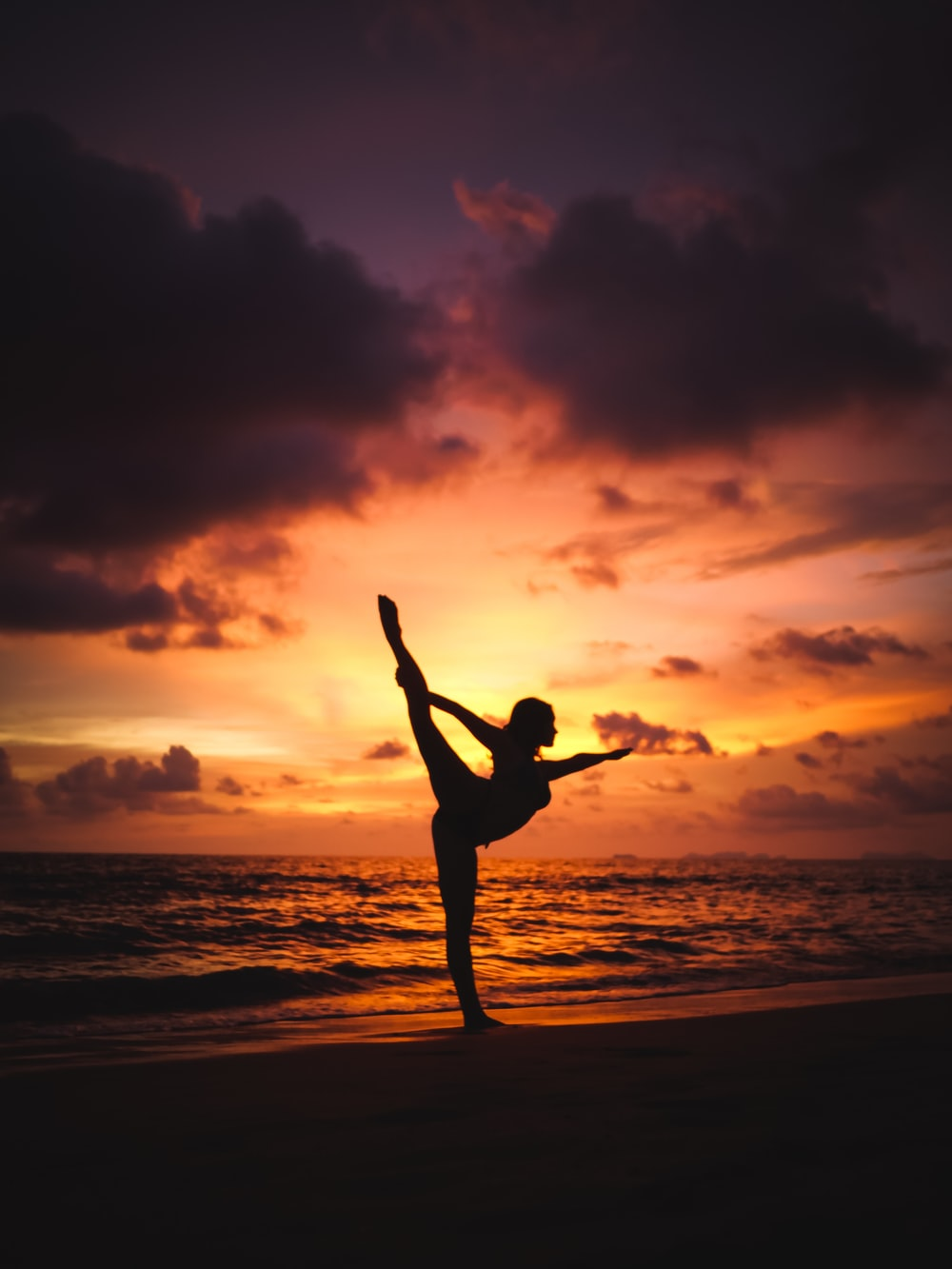 silhouette photography of woman stretching front of sea