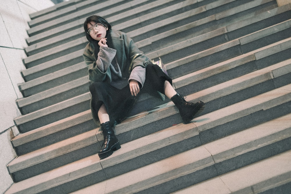 woman sitting on concrete stairs