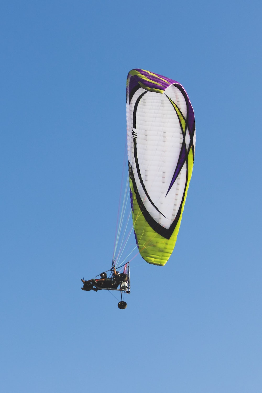 white and green vehicle with parachute flying during daytime
