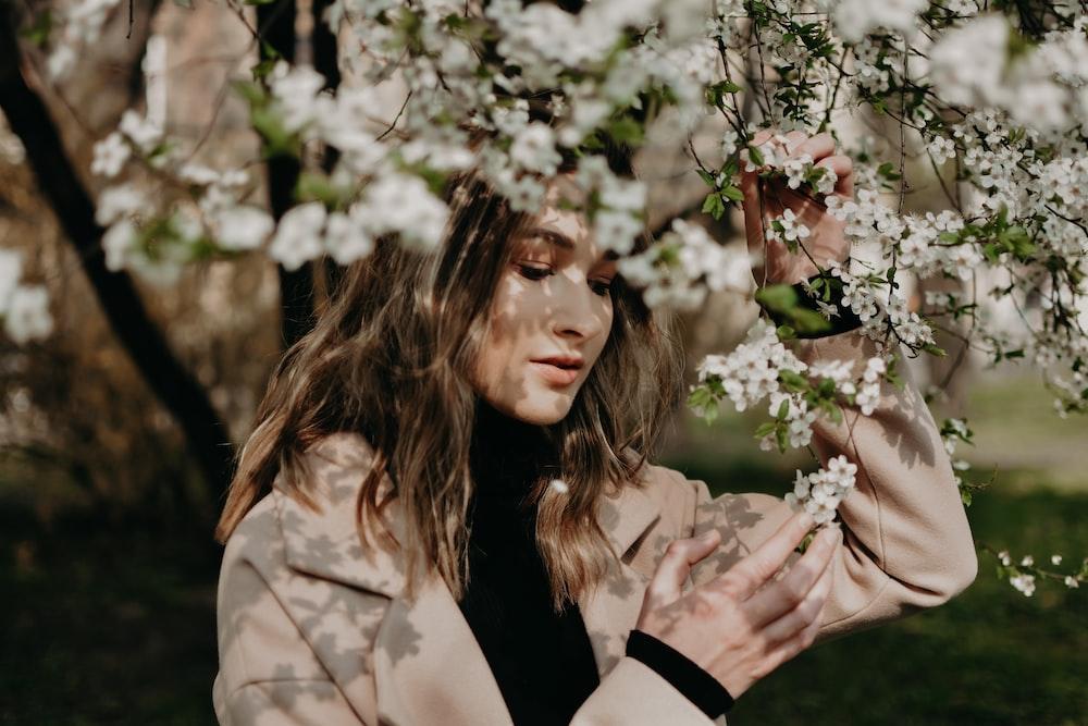 woman wearing brown suit jacket beside white flower