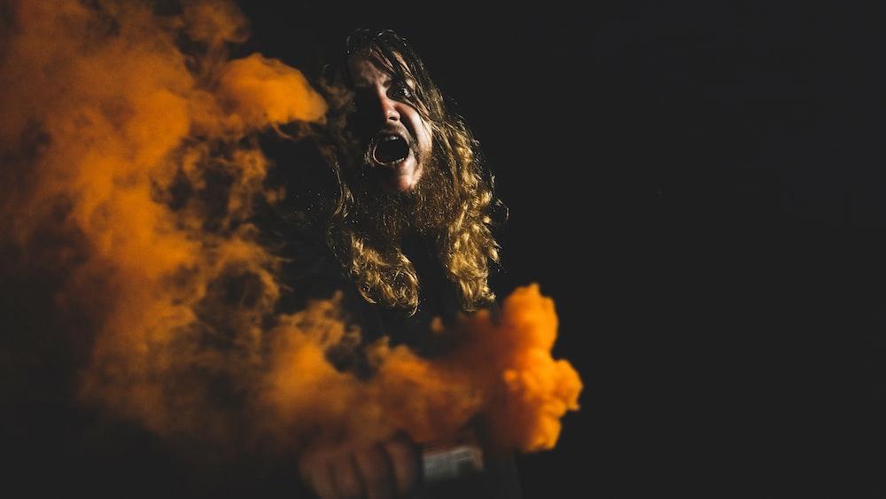 man holding orange smoke can