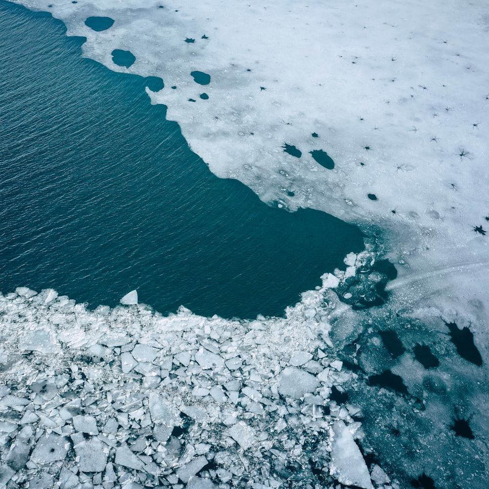 aerial photography of body of water surrounded by ice