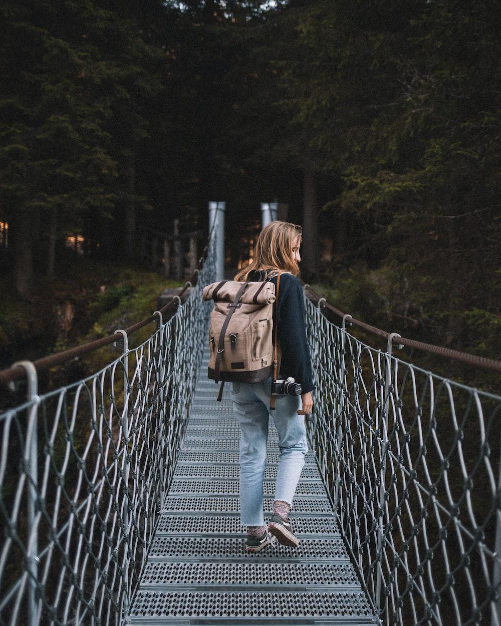 woman standing on gray hanging bridge