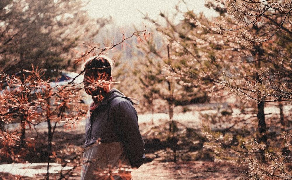 man standing near bush