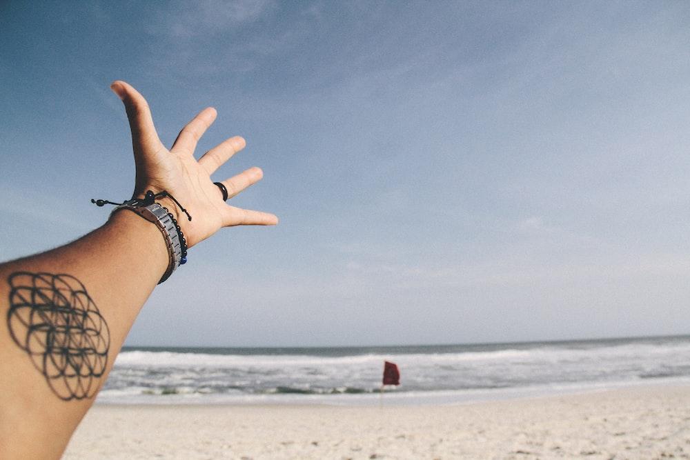 person raising it's hand near shoreline
