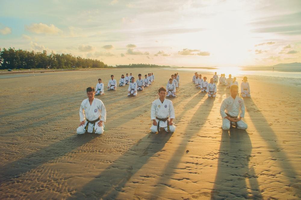 people kneeling on sandy ground