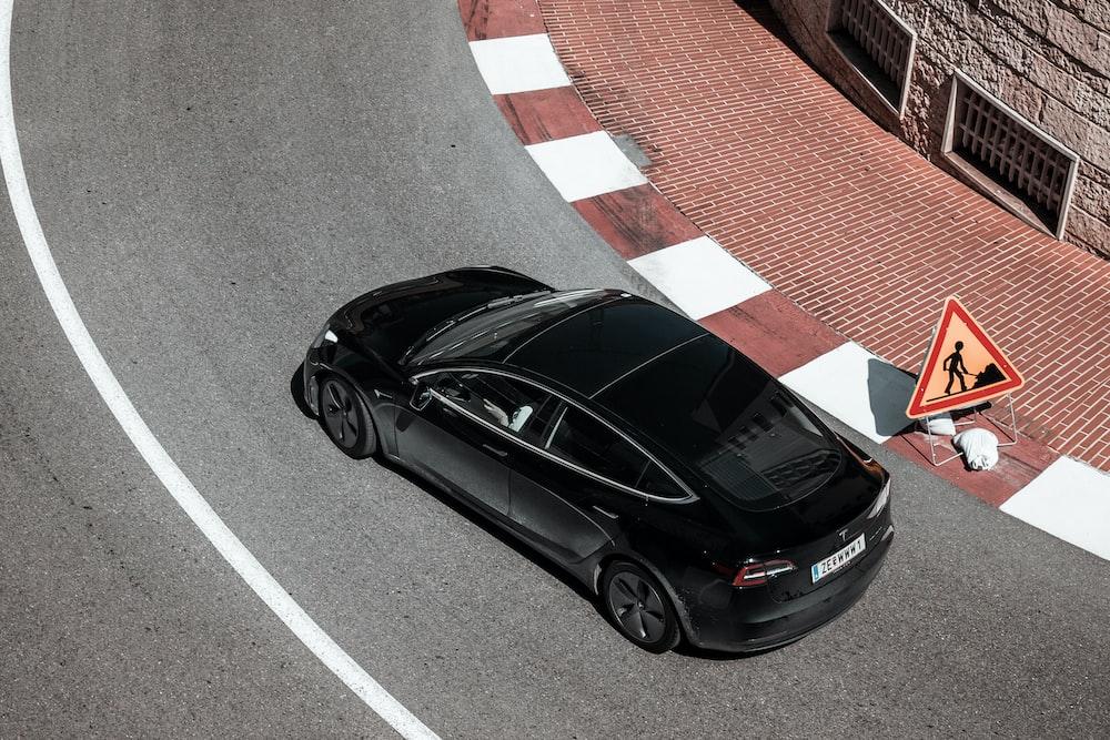 black sedan turning right curve