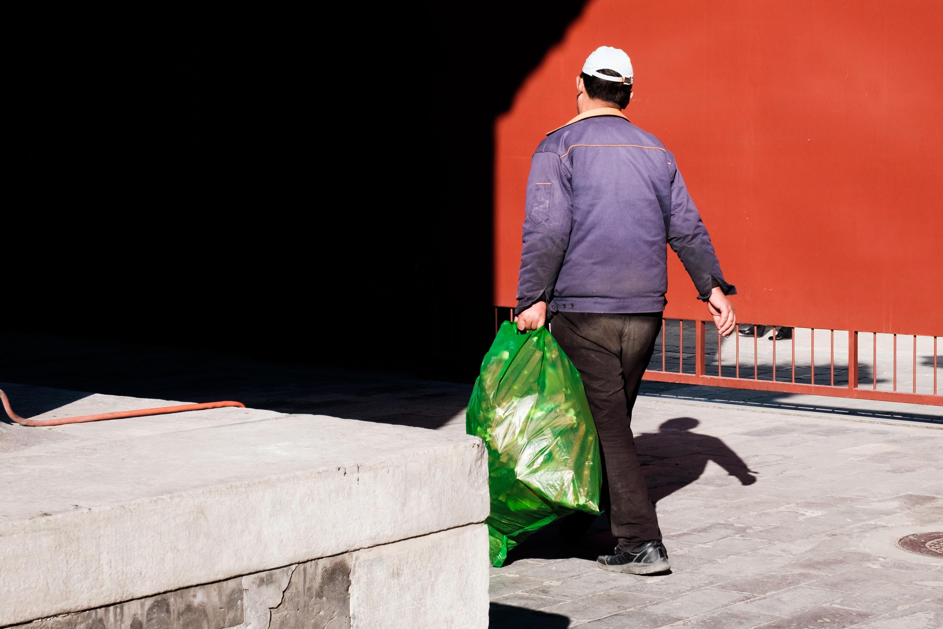 man carrying green plastic bag