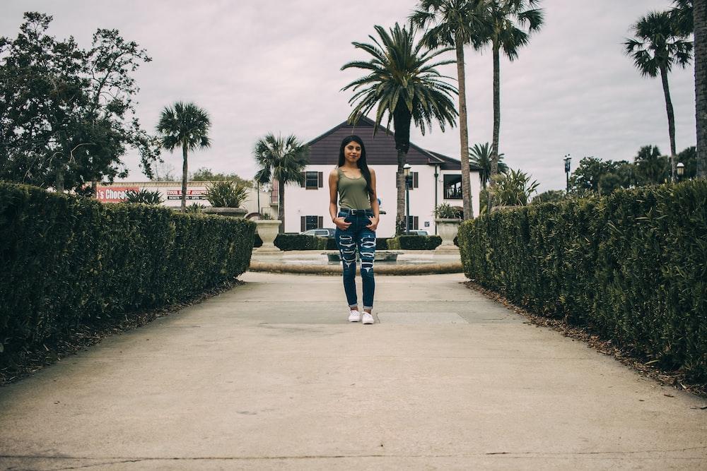 woman standing between hedges