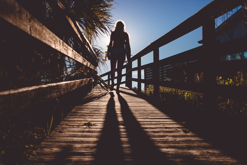 woman standing on brown bridge