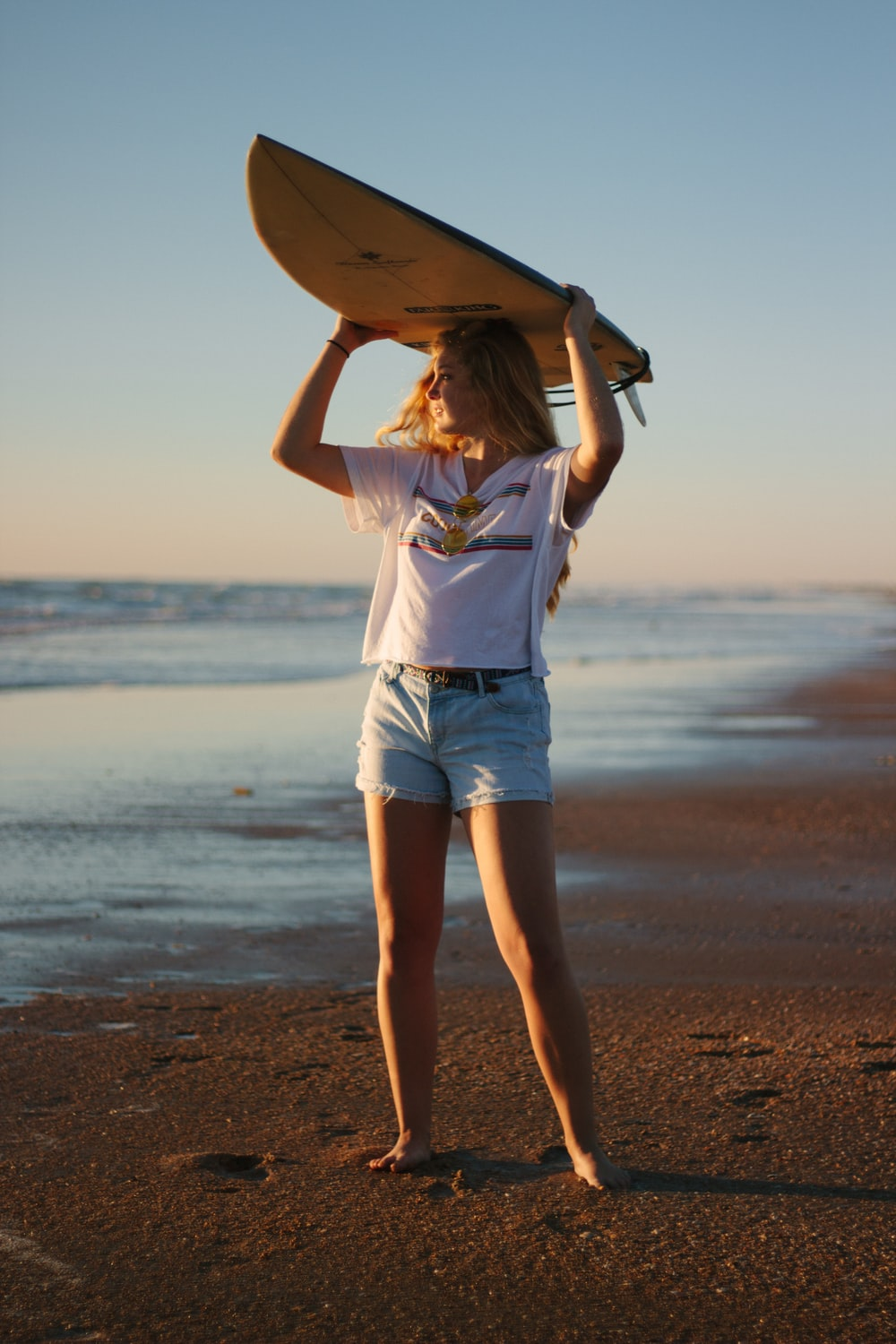 woman carrying surfboard