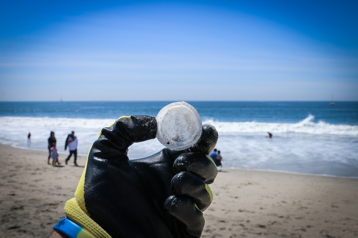 person holding round white ball near body of water during daytime