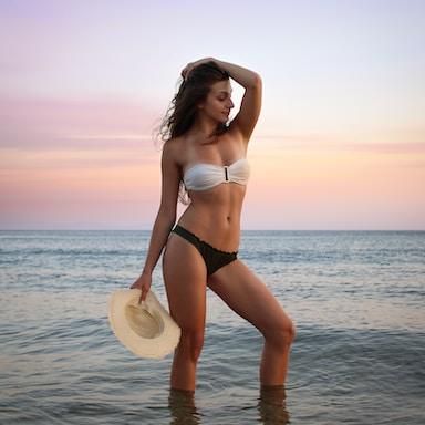 woman in bikini posing on seashore