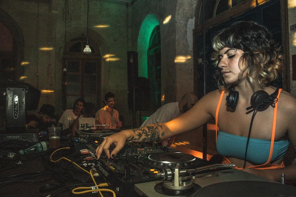 woman pkaying DJ controller at night