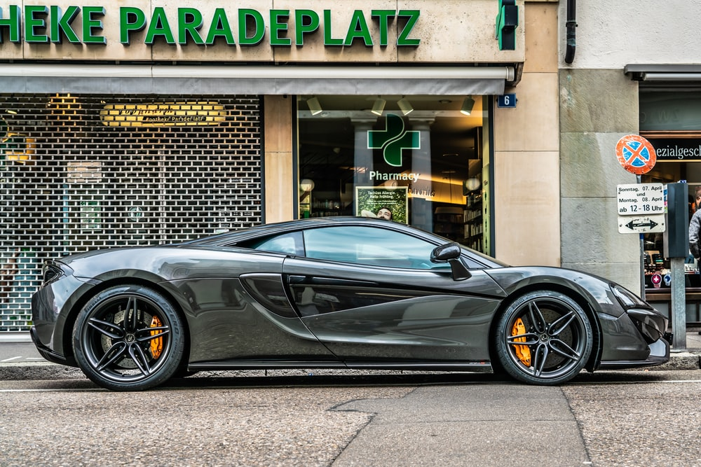 gray sports coupe parking beside store
