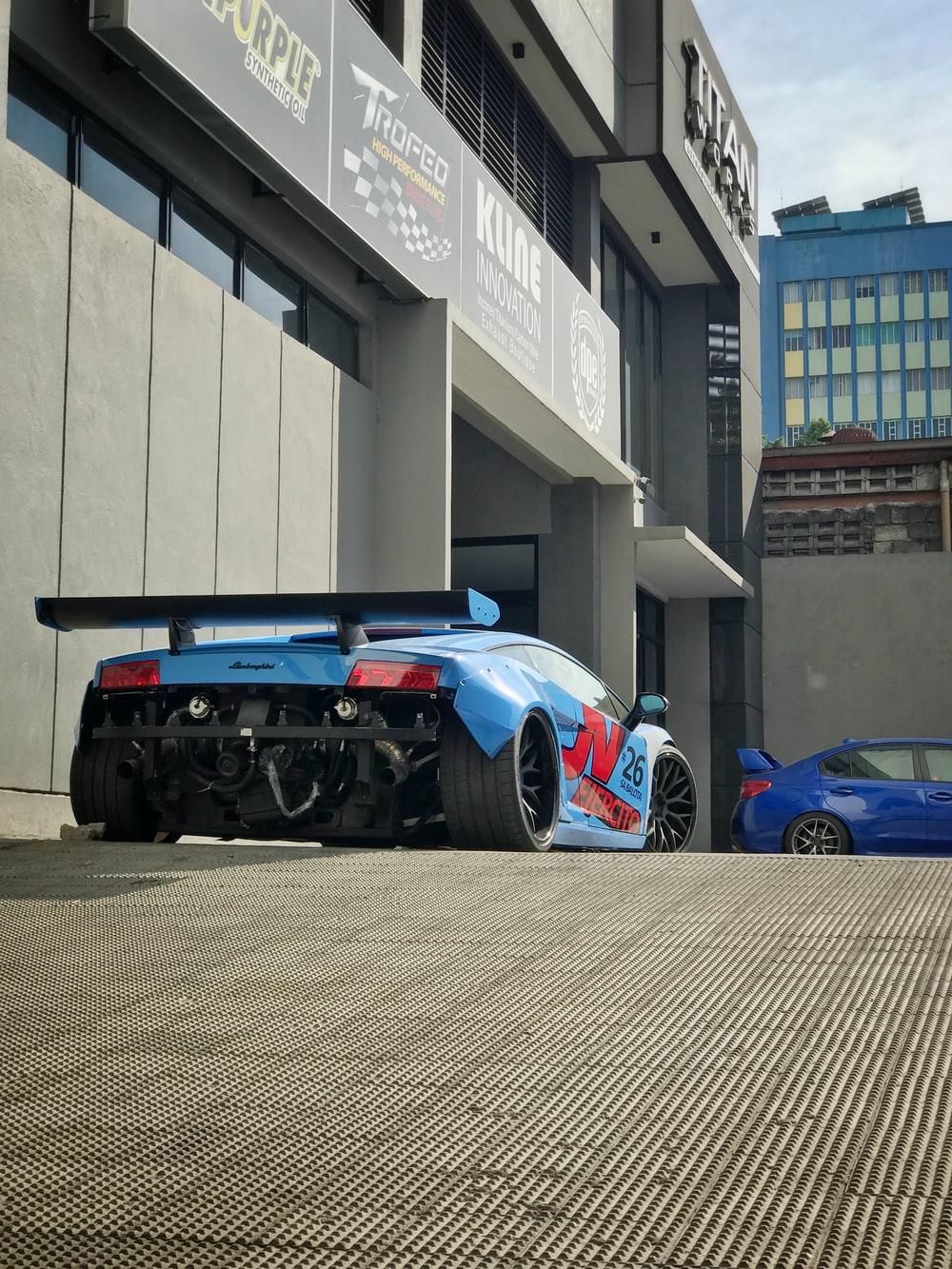blue car parked near building
