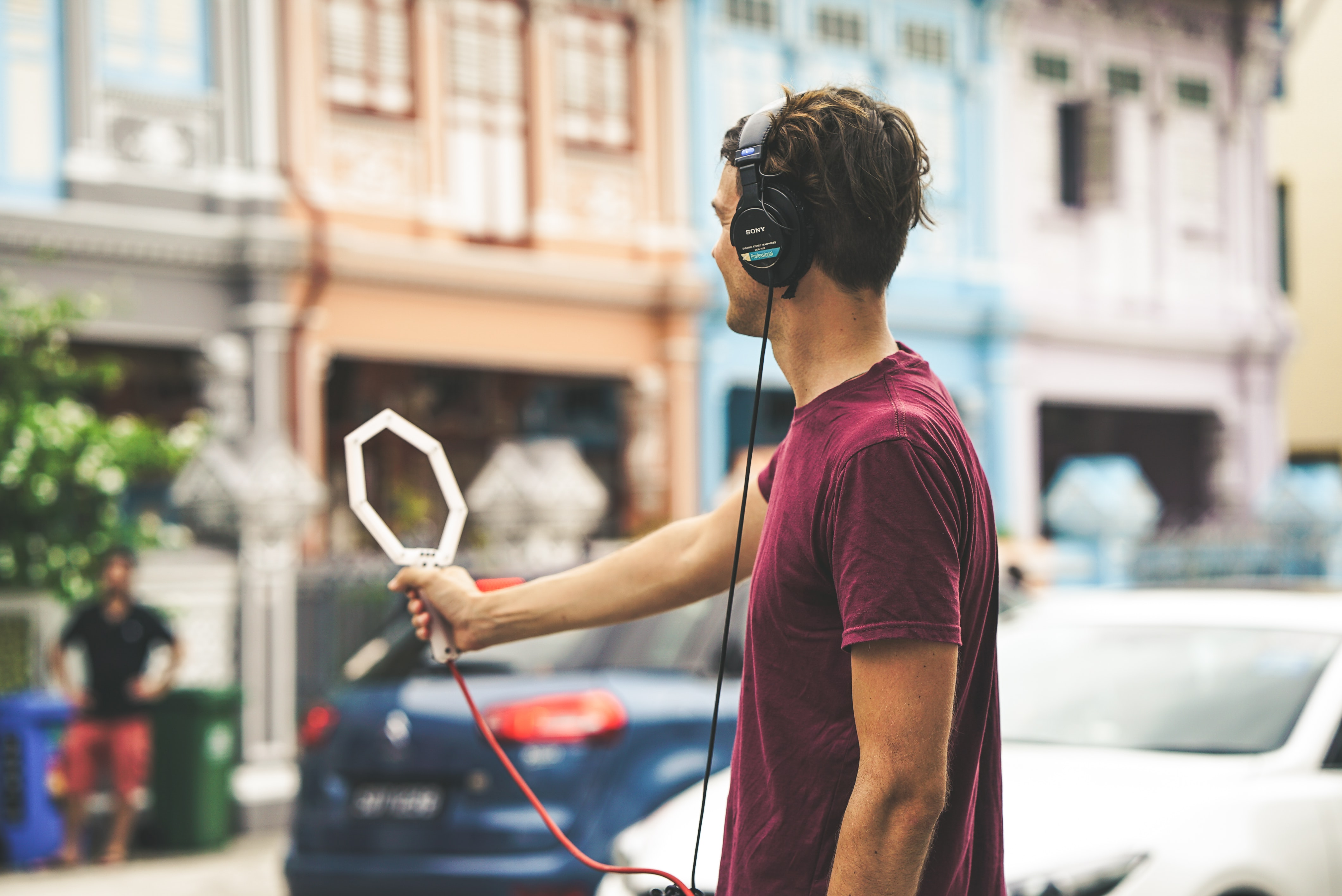 man wearing black corded headphones and holding mirror during daytime